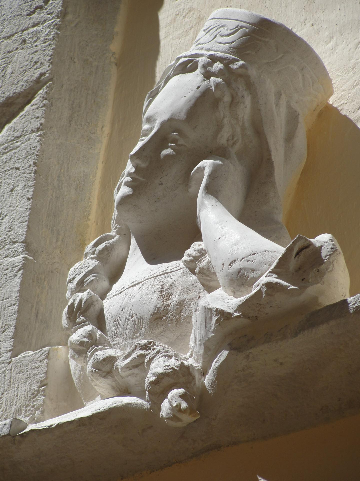 Sculpture sur pierre, relief d'une femme accoudée à sa fenêtre